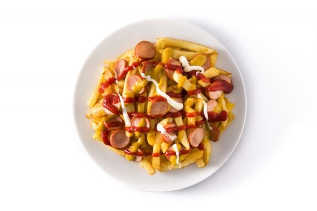 Salchipapa típico da américa latina. salsichas com batatas fritas, ketchup, mostarda e maionese isoladas na superfície branca vista superior