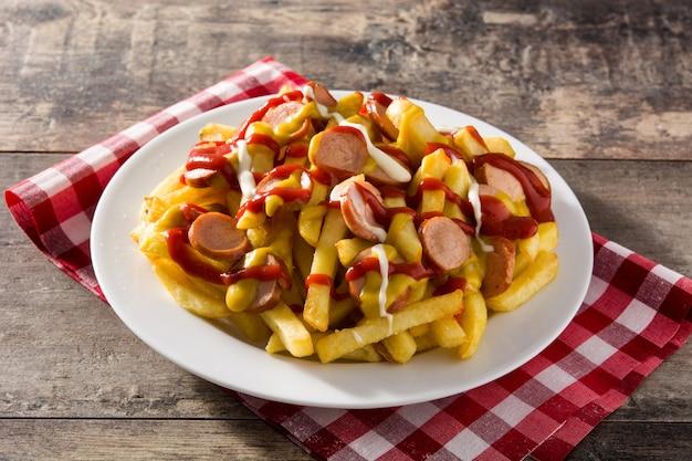 Salchipapa típico da américa latina. salsichas com batatas fritas, ketchup, mostarda e maionese na mesa de madeira