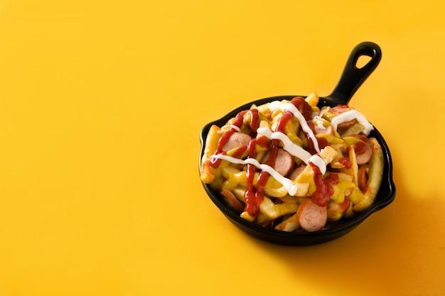Salchipapa típico da américa latina. salsichas com batatas fritas, ketchup, mostarda e maionese na panela de ferro e fundo amarelo.