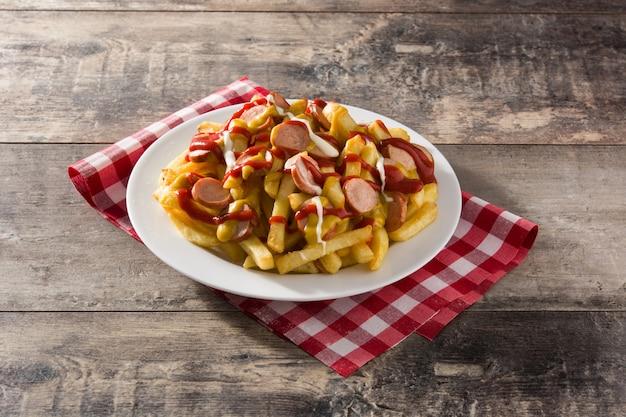 Salchipapa típico da américa latina. salsichas com batatas fritas, ketchup,