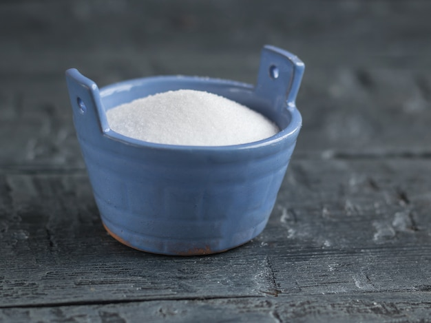 Saleiro azul em forma de um balde no sal de mesa rústico preto finamente