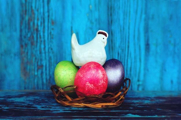 Saleiro de frango branco e ovos pintados multicoloridos sobre fundo de madeira vintage. ornamentos decorativos da páscoa. fundo. galinha galinha incuba os ovos no ninho. composição de páscoa.