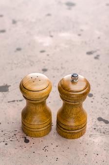 Saleiro e pimenteiro de madeira. tempero sal e pimenta em cima da mesa.