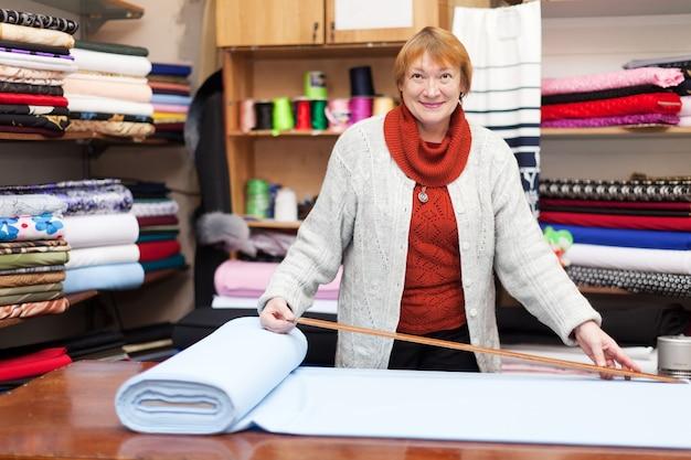 Salesclerk trabalha na loja de tecido