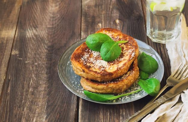 Salgadas torradas francesas com queijo parmesão e espinafre em superfície de madeira rústica