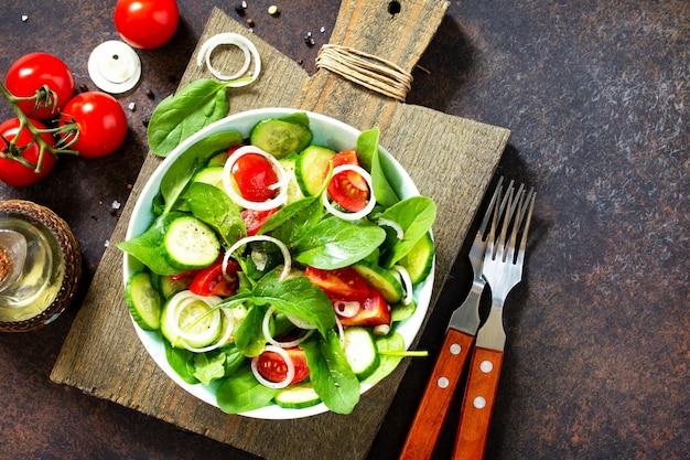 Salgadinho de vitaminas com legumes frescos e espinafre em uma mesa de pedra escura vista de cima plano