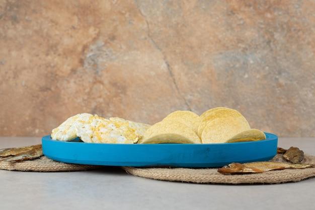 Salgadinhos crocantes em prato azul com peixe seco