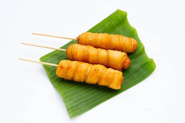 Salgadinhos de massa frita enrolados em salsicha em folha de bananeira