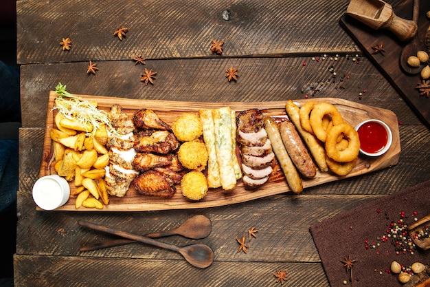 Salgadinhos fritos de cerveja salgada na tábua de madeira com molhos