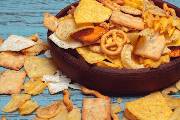 Salgadinhos. pretzels, batatas fritas, biscoitos na madeira. produtos não saudáveis