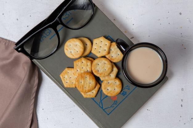 Salgadinhos saborosos com leite e óculos de sol na foto de fundo claro.
