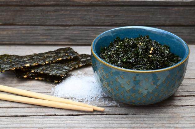 Salgado assado alga seca nori com sementes de gergelim em uma tigela azul