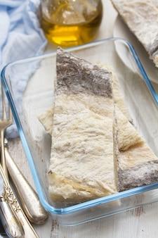 Salgado bacalhau seco cru no prato na superfície de madeira