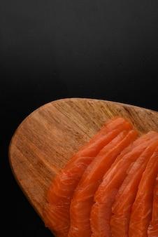 Salgado fumado salmão rosa cortado em uma tábua de madeira. mesa de madeira preta como um lugar para texto. copie o espaço.
