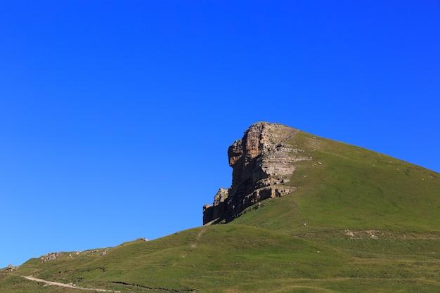 Saliência de pedra de uma crista rochosa contra o céu azul.