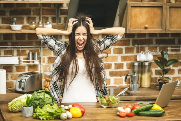 Salientou a bela jovem na cozinha. cansado em casa. mulher chorando.