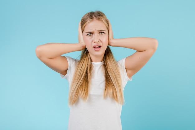 Salientou a jovem mulher com dor de cabeça, cobrindo as orelhas isoladas sobre o azul