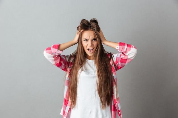 Salientou a jovem mulher com raiva, tocando a cabeça e gritando com a boca aberta na camisa quadriculada