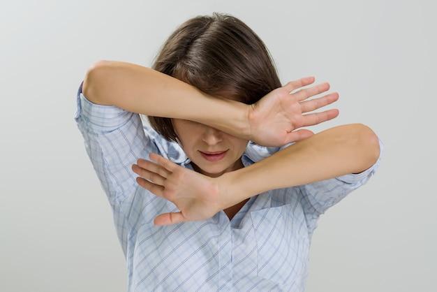 Salientou a mulher adulta, cobrindo o rosto com as mãos em casa