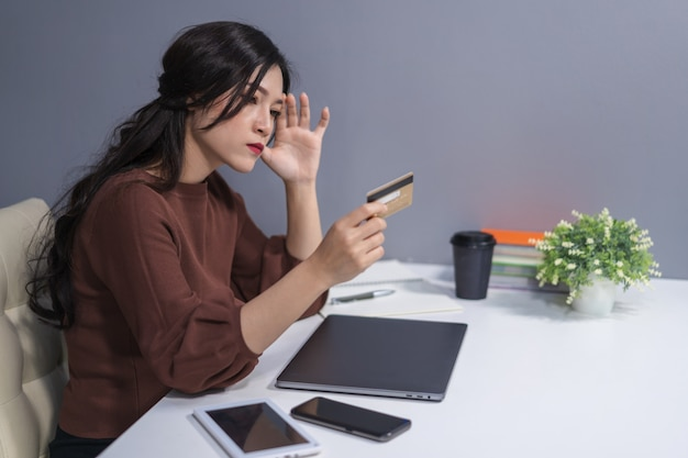 Salientou a mulher segurando o cartão de crédito com o computador portátil na mesa