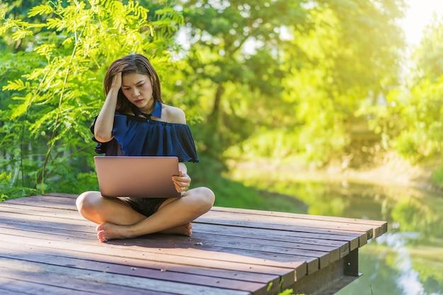 Salientou a mulher usando o computador portátil no cais de madeira