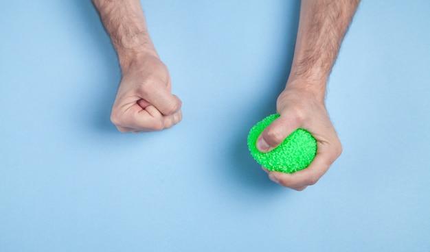 Salientou as mãos masculinas. mão segurando uma bola de estresse verde sobre fundo azul