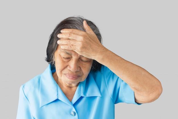 Salientou exausta avó tendo forte dor de cabeça de tensão em um fundo cinza