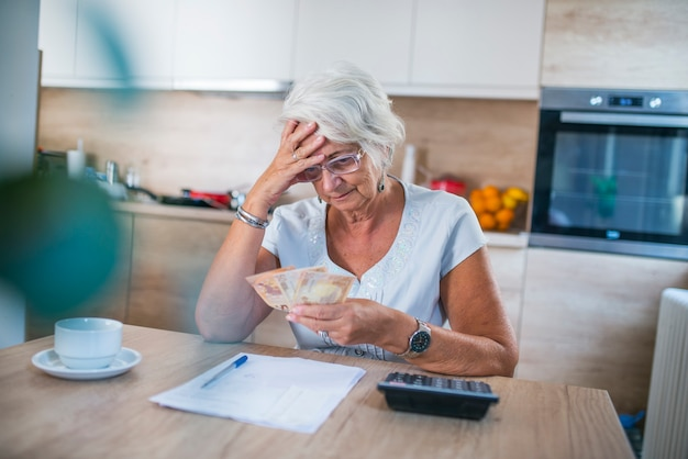 Salientou mulher sênior tendo uma dor de cabeça ao ler o aviso de conta bancária para pagar