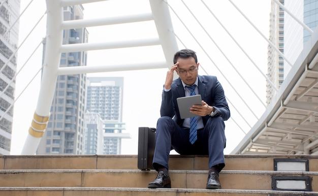 Salientou o empresário asiático está sentado sobre o stirs usando tablet digital à procura de um emprego