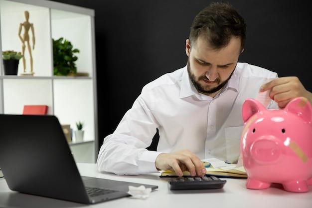 Salientou o empresário calcular contas em casa escritório cofrinho quebrado na mesa