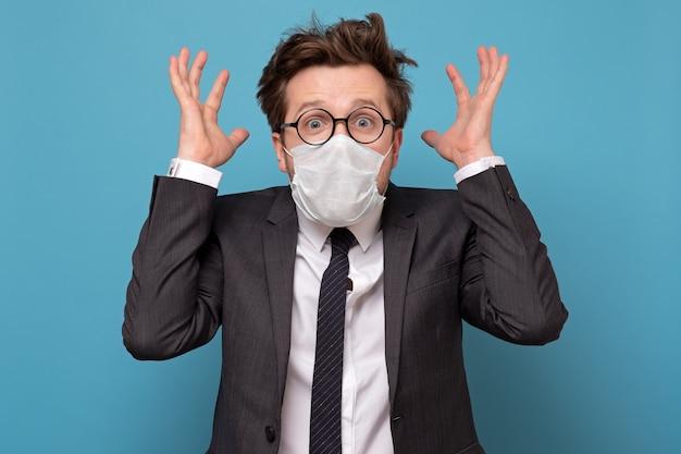 Salientou o homem caucasiano em máscara médica e óculos em pânico