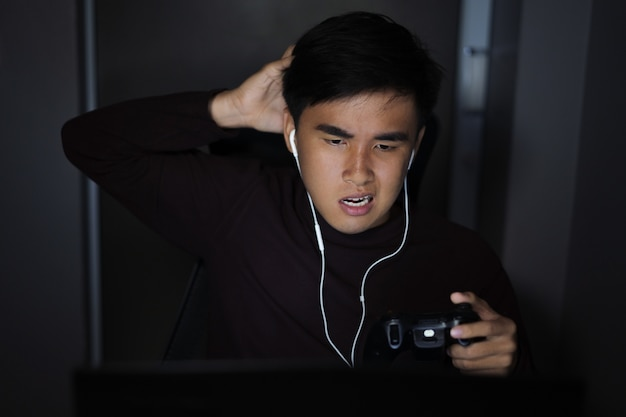 Salientou o homem deprimido usando joystick para jogar jogos