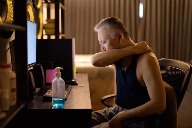 Salientou o homem japonês maduro, cobrindo a tosse com o cotovelo enquanto trabalhava em casa