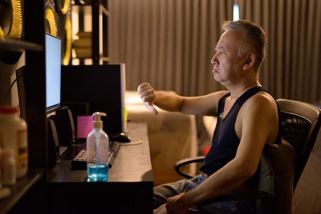 Salientou o homem japonês maduro, usando o computador e dando os polegares para baixo em casa