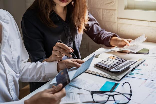 Salientou o jovem casal verificar contas, impostos, saldo da conta bancária e calcular despesas na sala de estar em casa