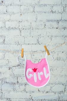 Saliva rosa de criança pequena em uma corda em um fundo de parede de tijolo branco