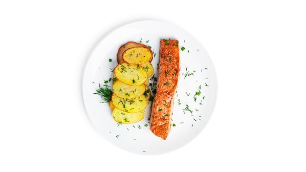 Salmão assado e batatas com ervas na chapa branca isolada no branco.