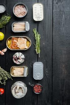 Salmão, atum, cavala de truta e anchova - conjunto de conservas de peixe em latas, sobre fundo preto de mesa de madeira com ervas e ingredientes, vista de cima plana lay, com copyspace e espaço para texto