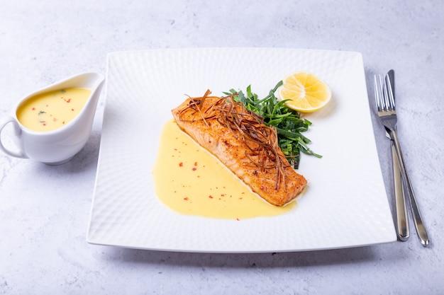 Salmão com molho beurre blanc, espinafre e limão guarnecido com alho-poró prato francês