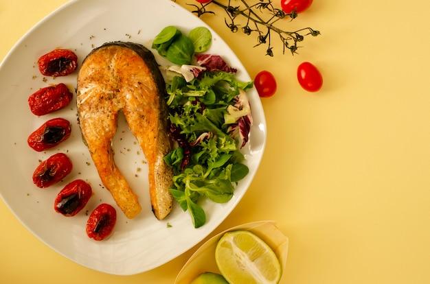 Salmão com tomate cereja assado e folhas de salada mista e metades de limão. comida mediterrânea. vista do topo