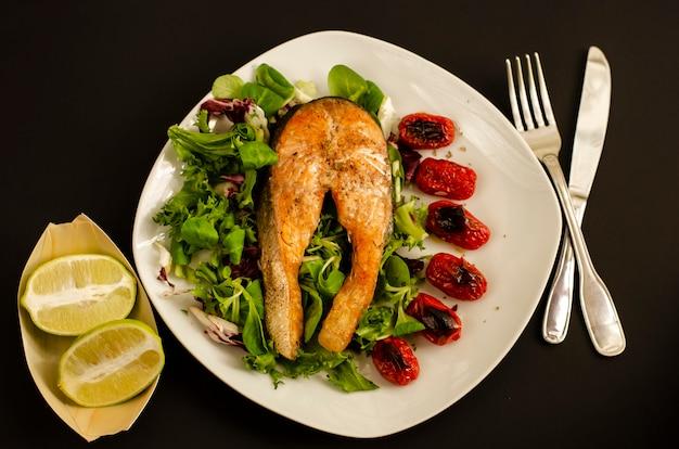 Salmão com tomate cereja assado e folhas de salada mista e metades de limão
