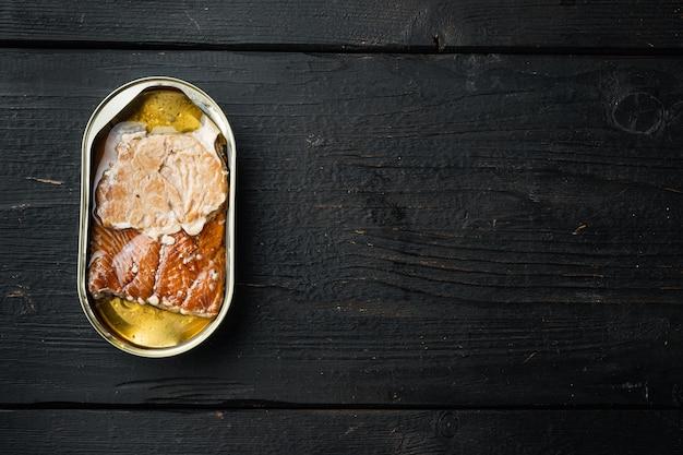 Salmão, conservas de peixe conjunto de peixe defumado em lata, em lata, na mesa de madeira preta