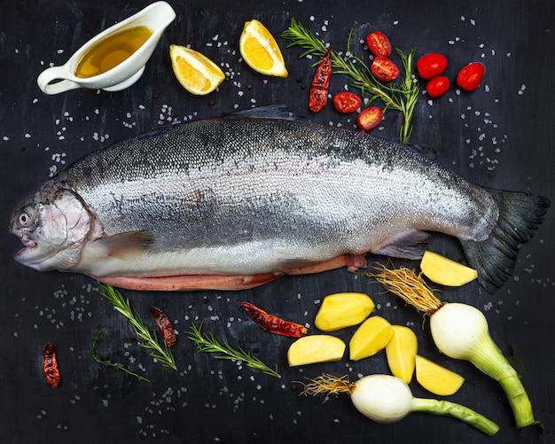 Salmão cru inteiro. peixe fresco com especiarias, tomate, cebola, limão, batata e azeite