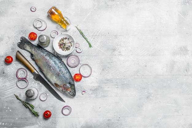 Salmão de peixe cru com especiarias e anéis de cebola roxa em uma mesa rústica.
