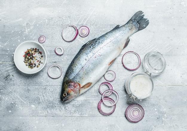 Salmão de peixe cru com especiarias e anéis de cebola roxa. sobre um fundo rústico.