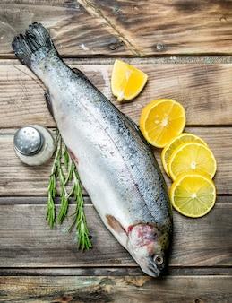 Salmão de peixe do mar cru com rodelas de limão, ervas e especiarias. em madeira