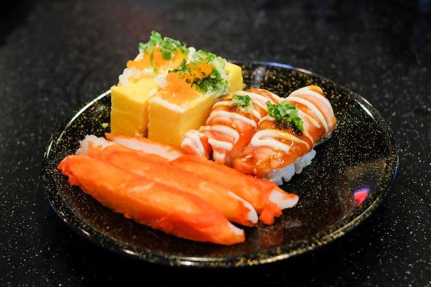 Salmão de toro grelhado (nigiri de saquê), omelete rolada (tamagoyaki), sirva de vara de caranguejo de imitação
