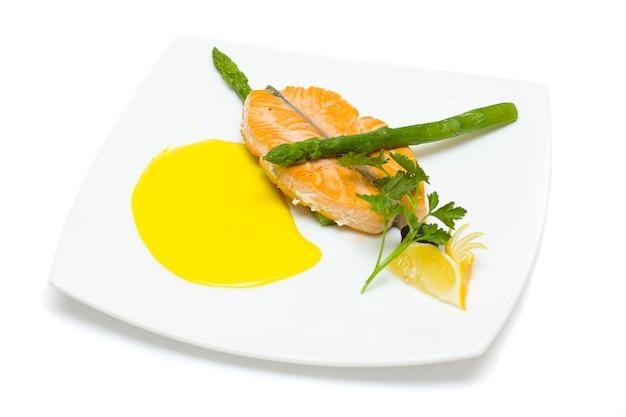 Salmão e espargos com limão, enfeite de endro isolado no fundo branco