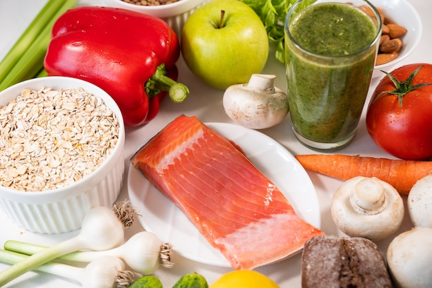 Salmão fresco apetitoso e outros ingredientes para cozinhar em uma mesa branca e uma dieta saudável