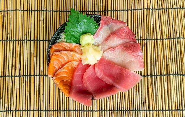 Salmão fresco, atum e hamachi cru sobre arroz coberto - comida japonesa